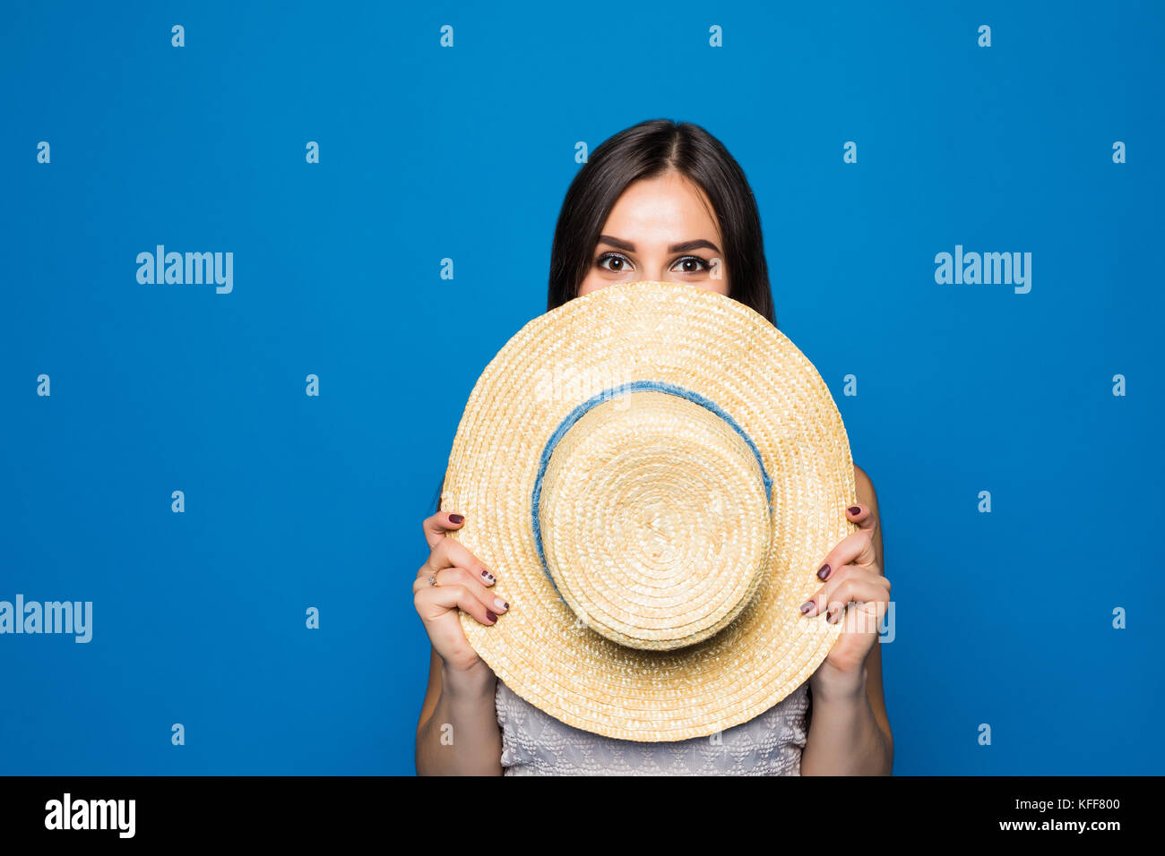 6f97364c860 Portrait of cute woman covering face with round hat on blue Stock ...
