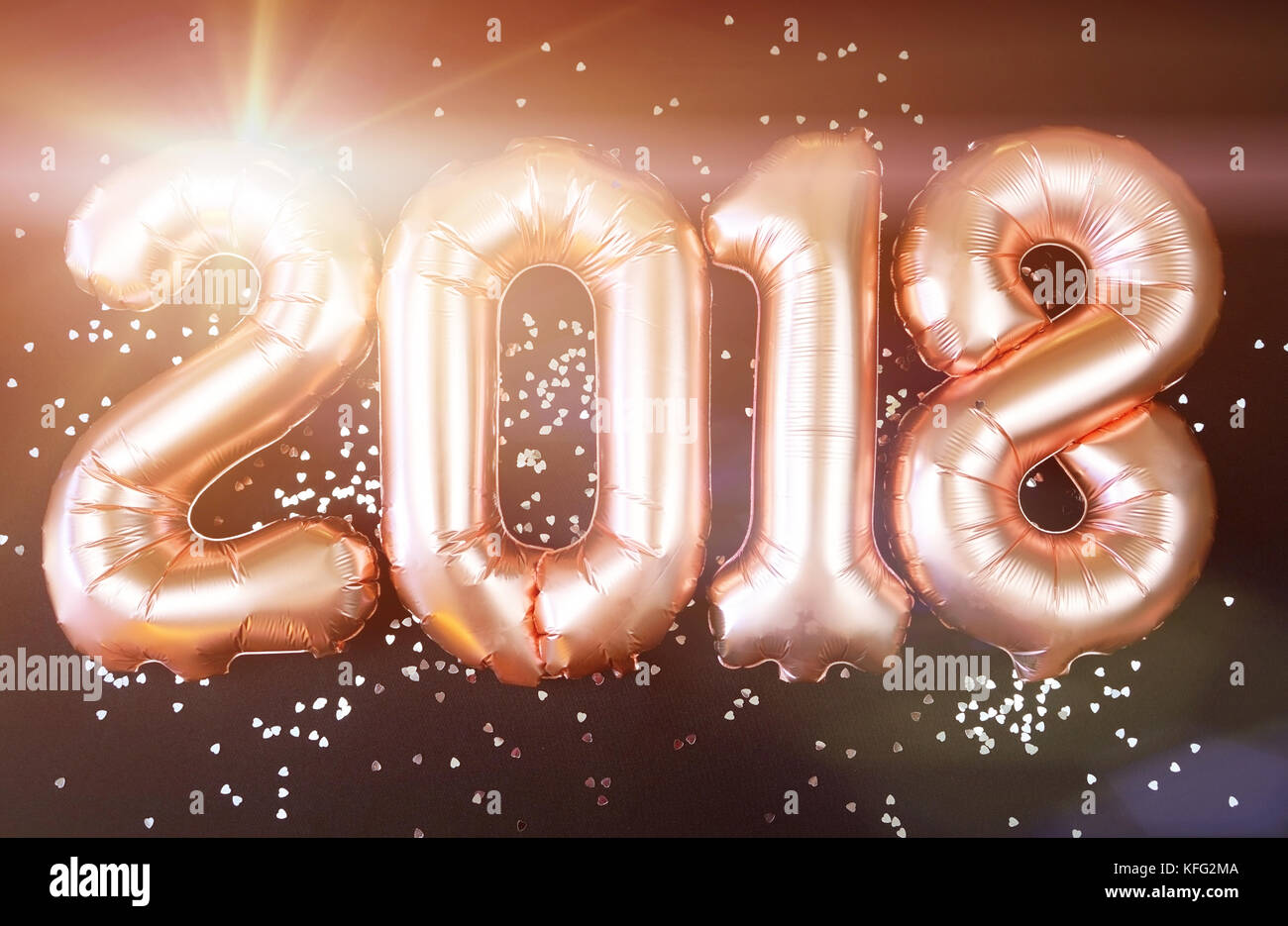 happy 2018 gold new year balloons with glitter stars on black background with lens flare