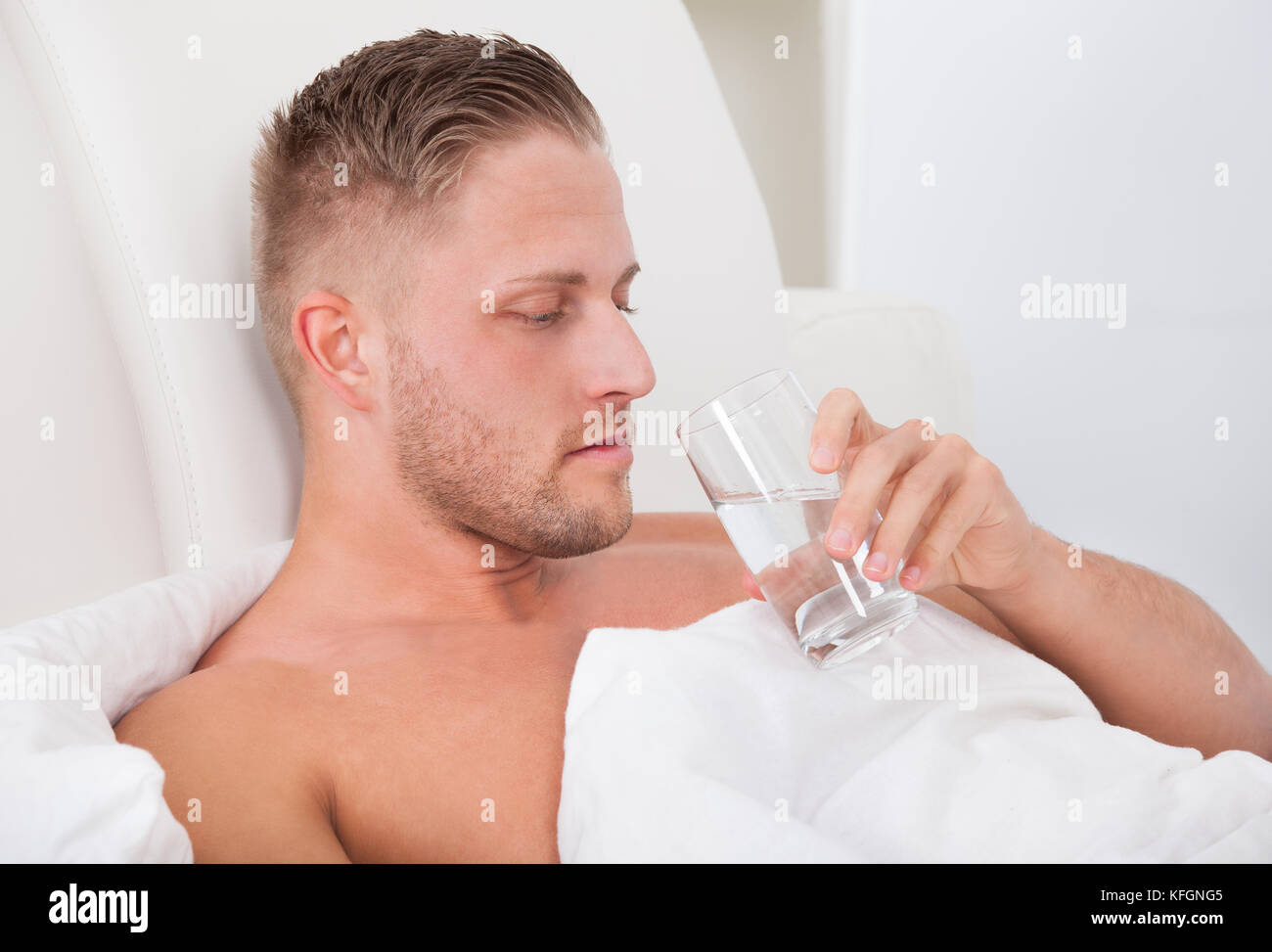 Man Lying In Bed Propped Up Against The Pillows Drinking A Glass Of