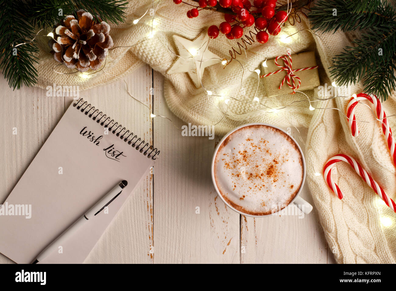 winter holidays background with cup of hot coffee wish list and christmas decorations and lights flat lay with copy space