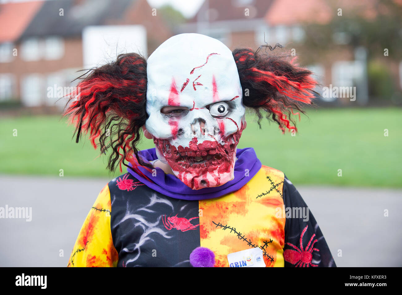a child wearing a a scary clown mask for halloween