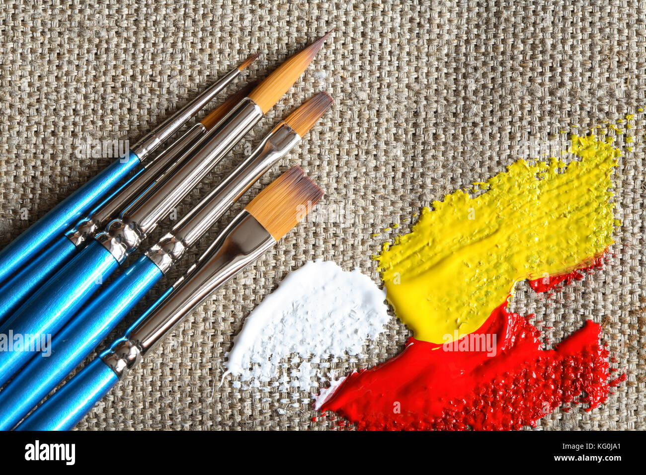 set of paintbrushes and color paint on canvas background stock photo