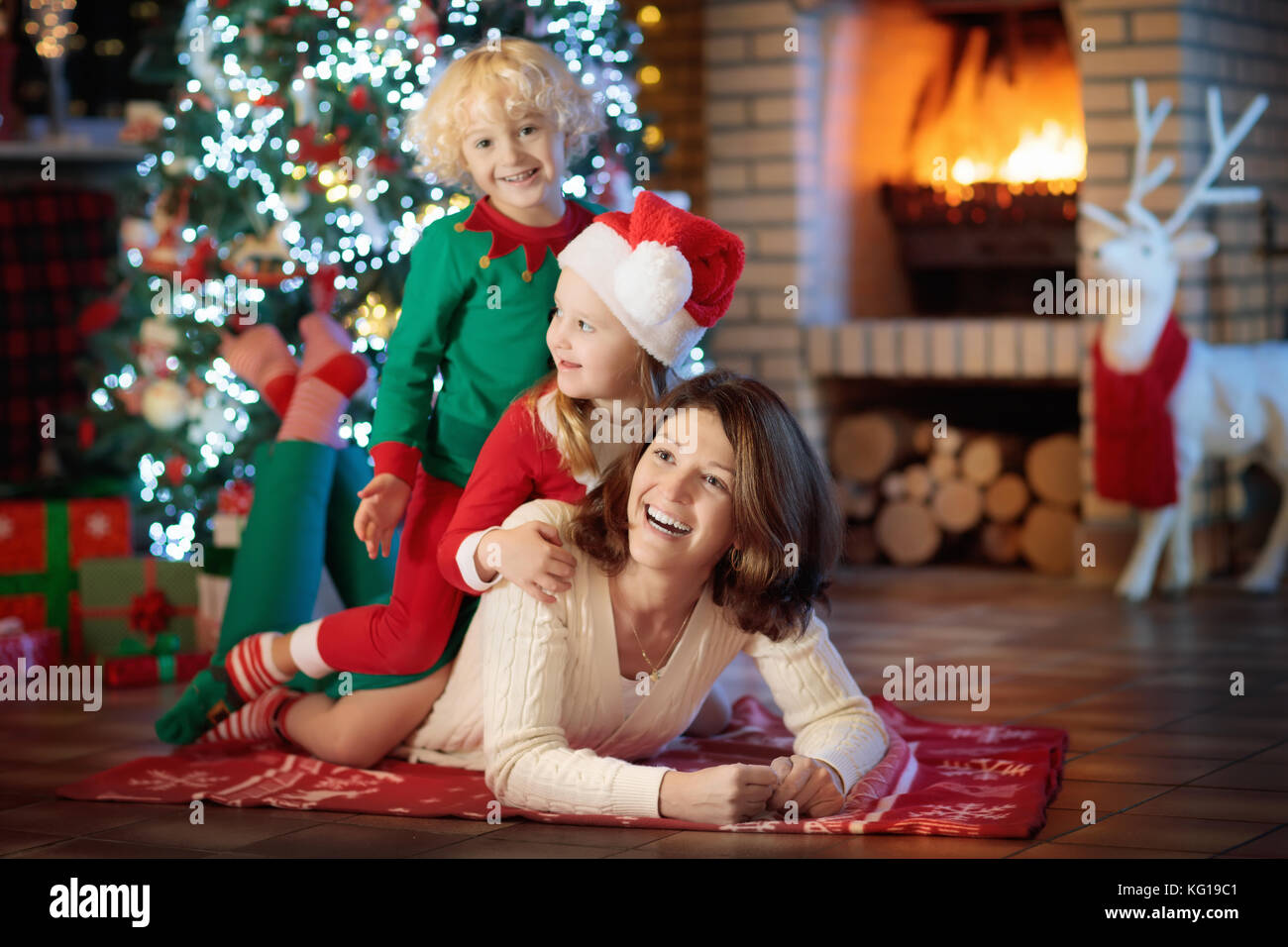 Family with kids at Christmas tree and fireplace. Mother and ...