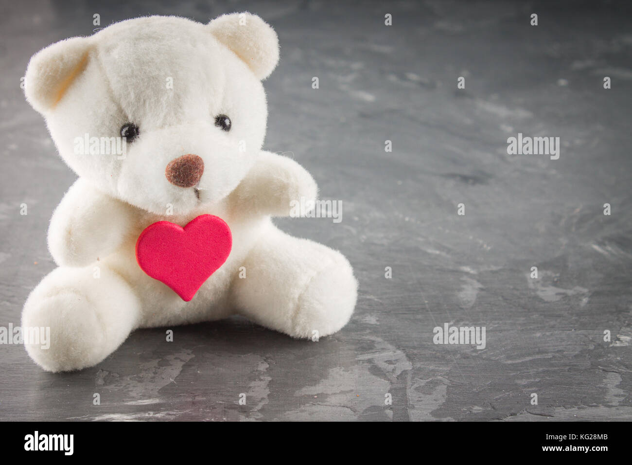 White teddy bear with love letter on red heart on gray background ...