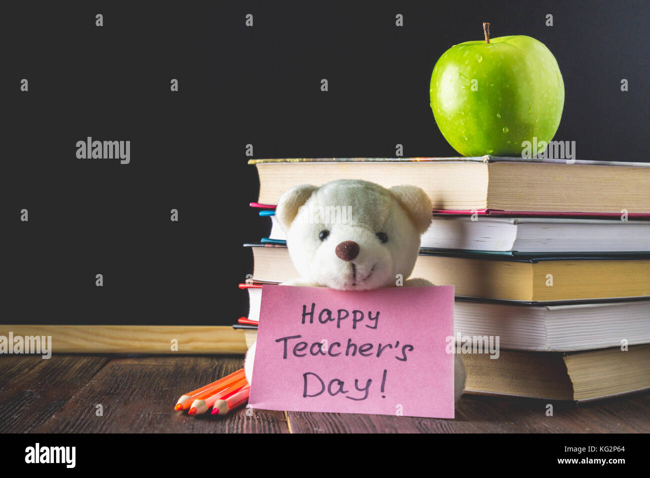 Objects On A Chalkboard Background Books Green Apple Bear With Sign Happy Teachers Day Pencils And Pens In Glass