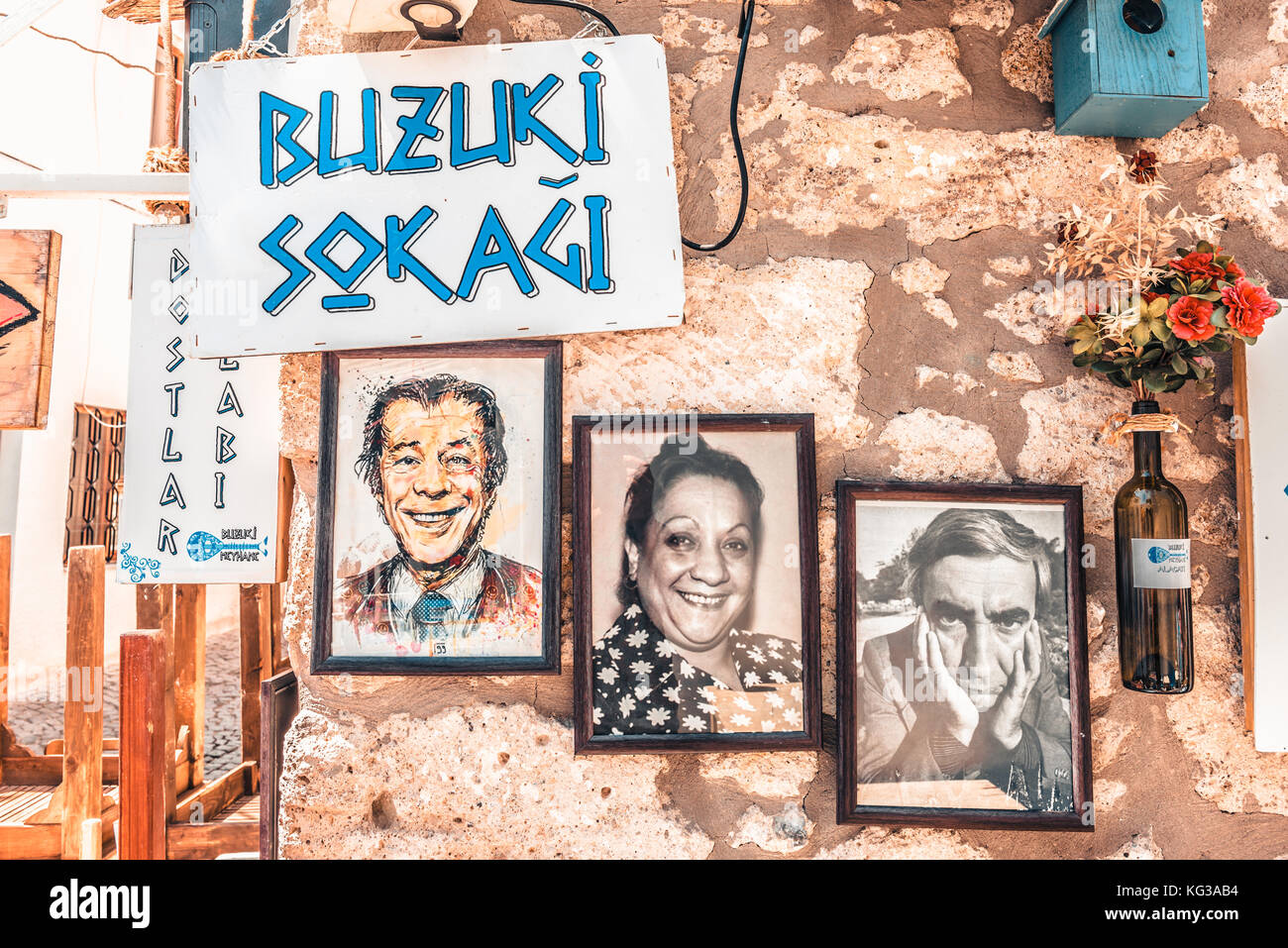 Frames with photos of famous Turkish people on white stone wall and ...