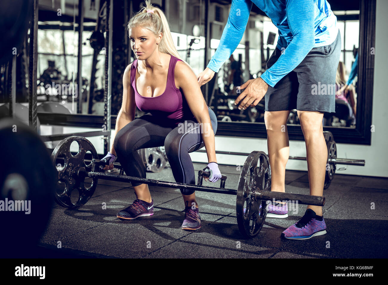 Attractive blonde woman doing trap bar deadlift exercise with help