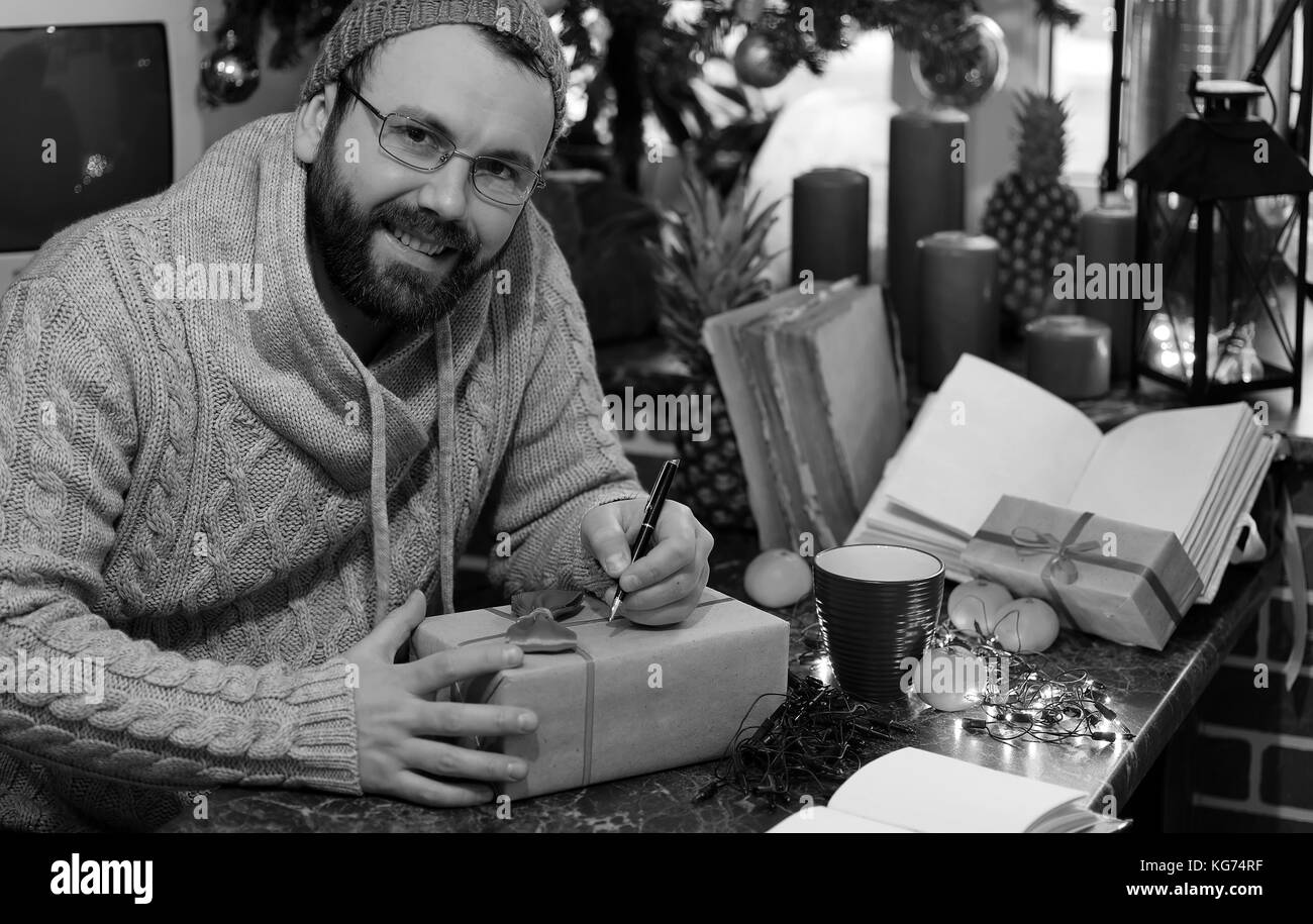 beard man writing christmas gifts on a table with old books Stock ...