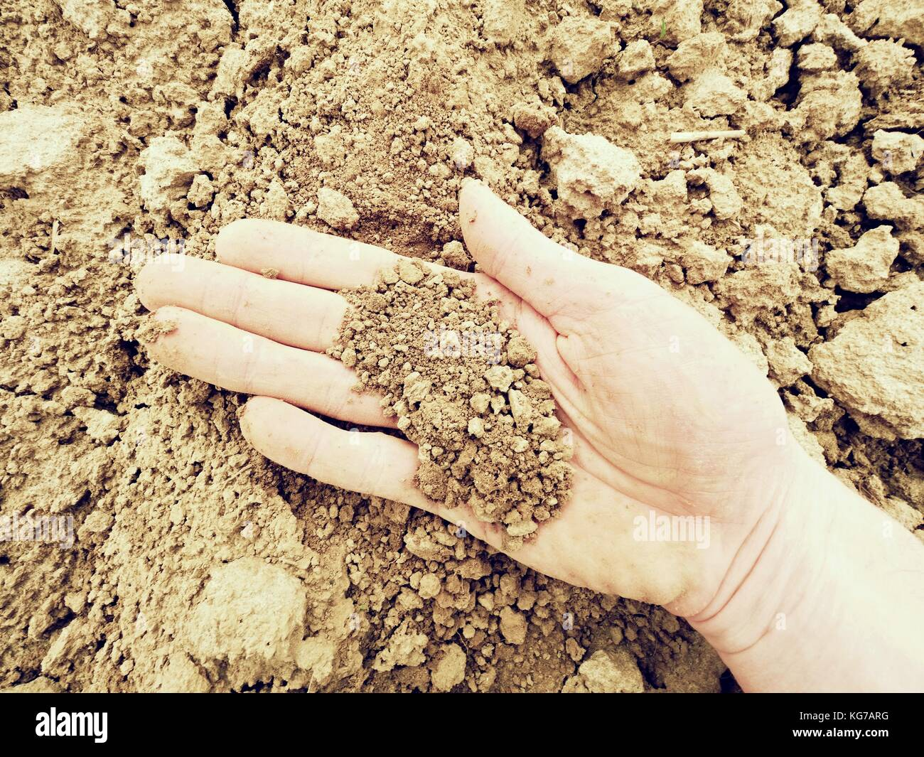 pink skin hand looking for something in wet brown clay in the field