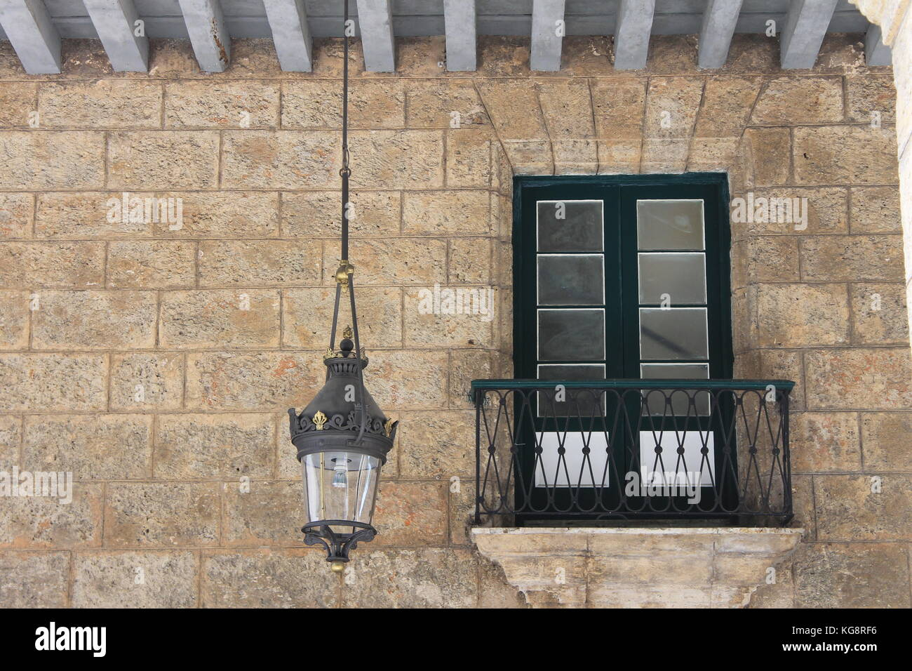 Doors opening unto a Juliet balcony in a stone wall in an old Spanish style building & Doors opening unto a Juliet balcony in a stone wall in an old ...