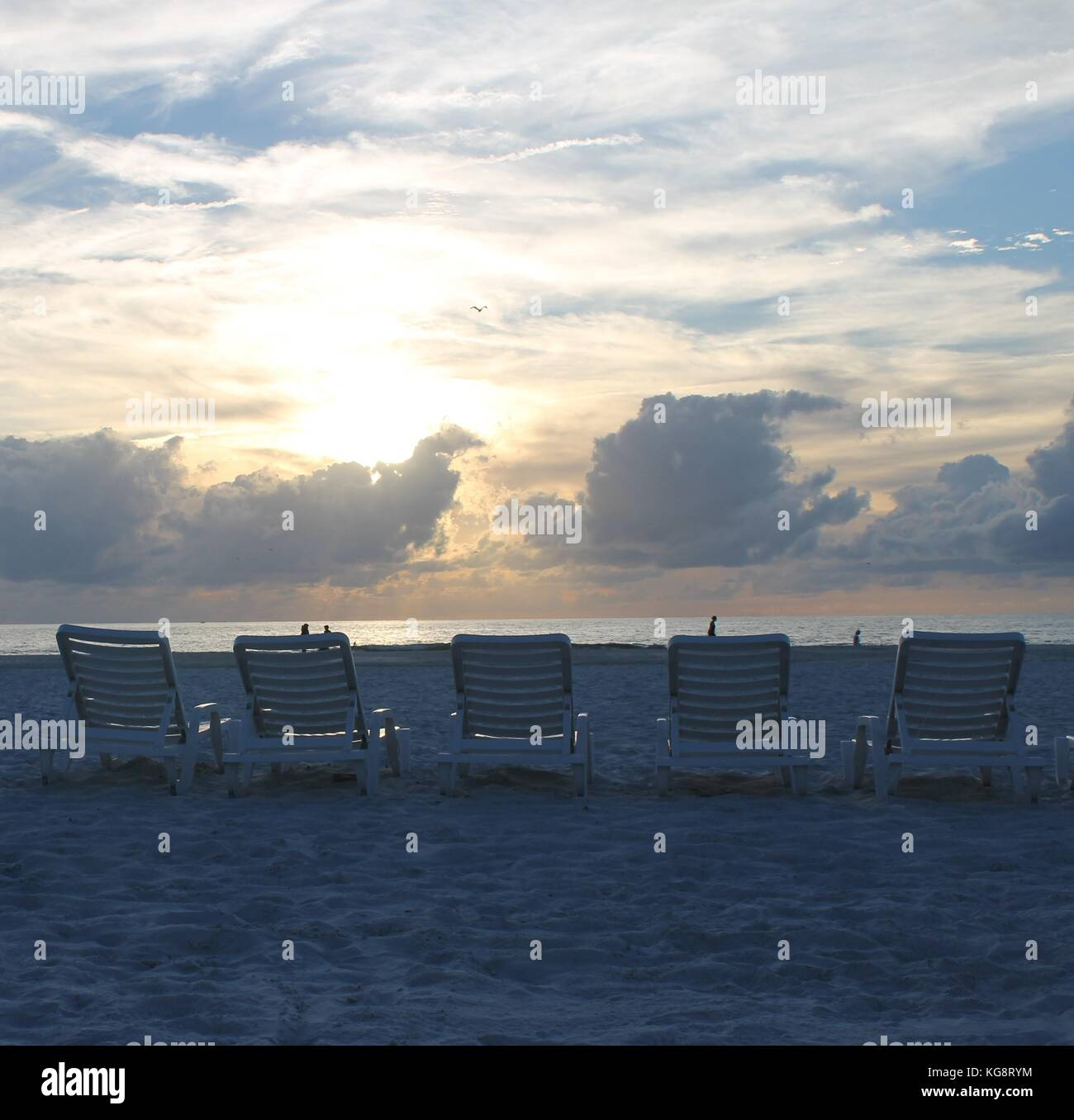 Sunset over the Gulf of Mexico from beach with beach chairs St