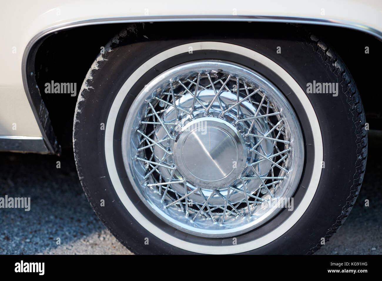 a close up of shiny vintage style chrome car wheels with spokes stock image