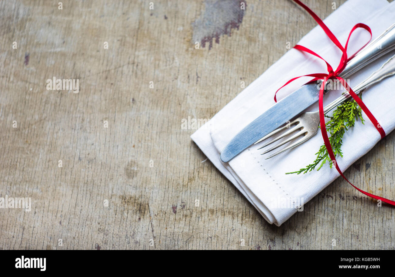 Napkin with red ribbon and vintage silverware on rustic wooden table ...
