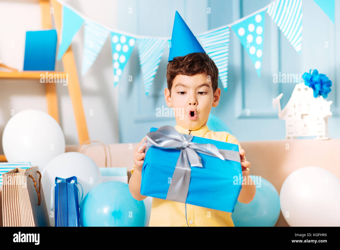 Little Boy Looking At His Birthday Gift With Surprise