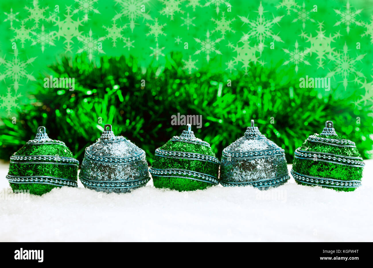 Green and blue and silver Christmas balls in snow with tinsel and ...