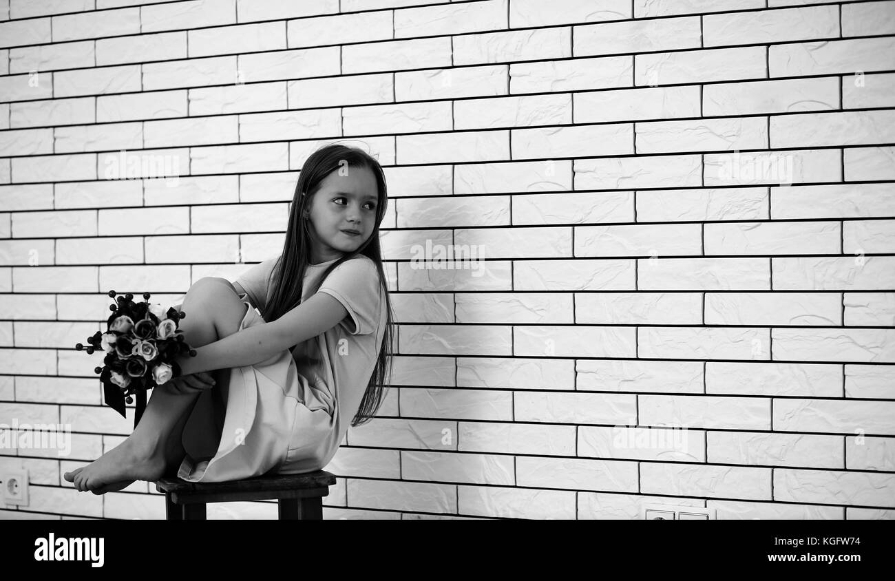 Black child sitting in chair - Little Girl On A Chair Black And White Stock Image