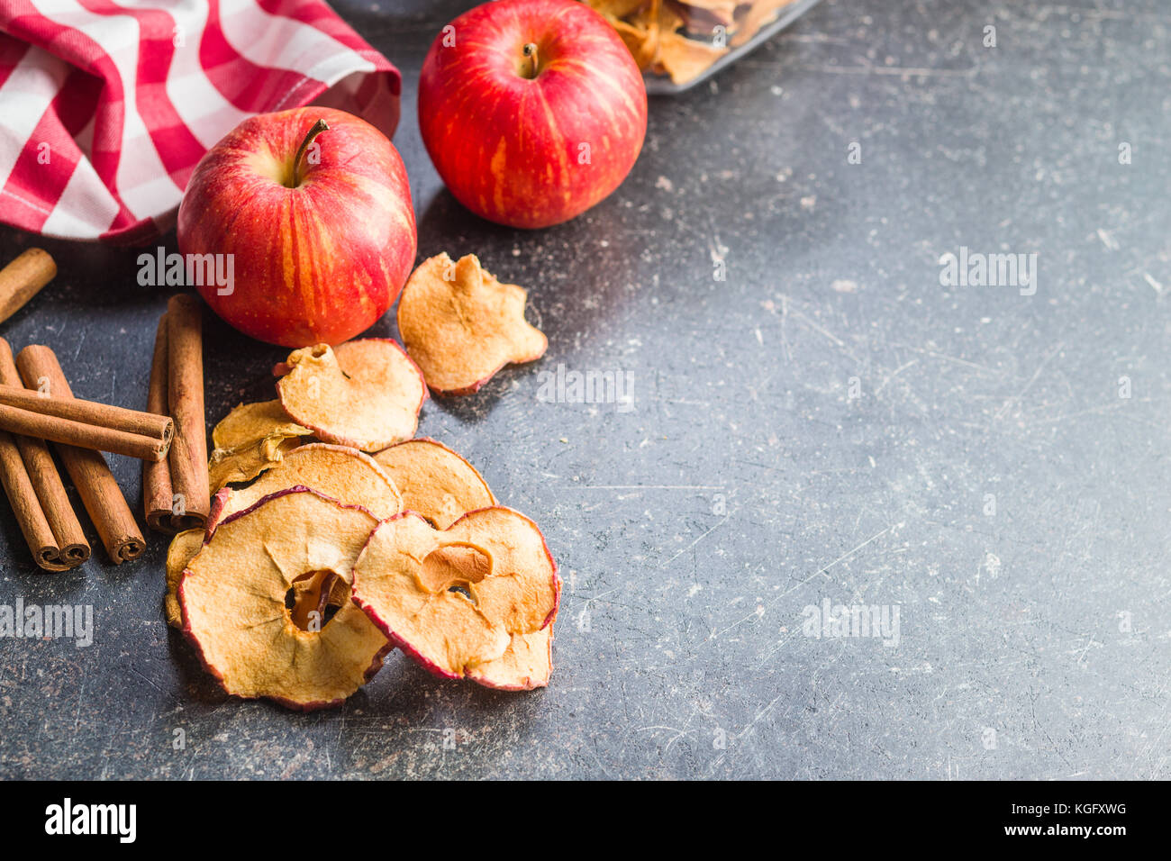 Dried apple slices and cinnamon on kitchen table Stock Photo ...