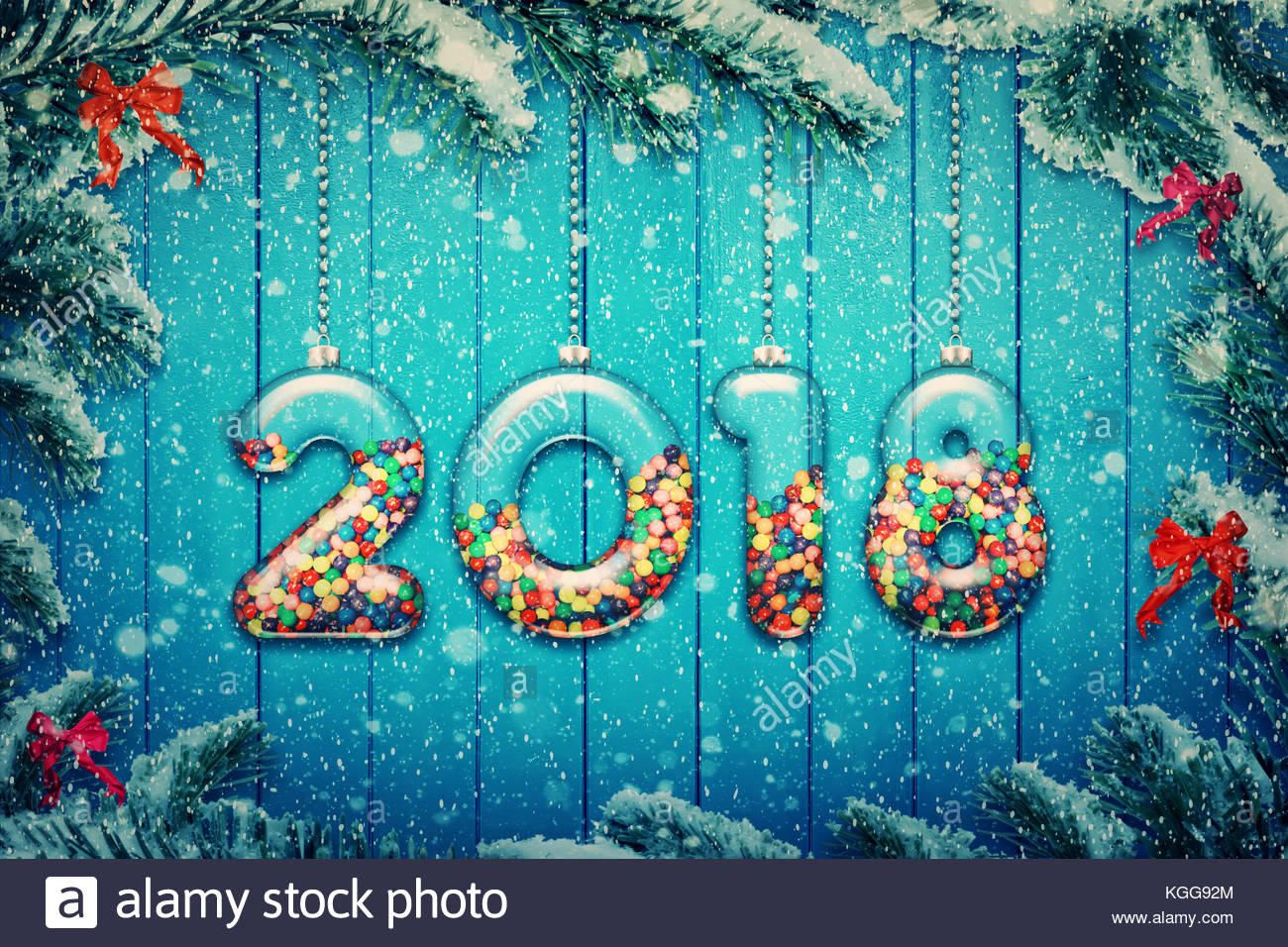 happy new year 2018 background set of transparent glass with multicolored candy and sweets hang on a snowy christmas tree branch
