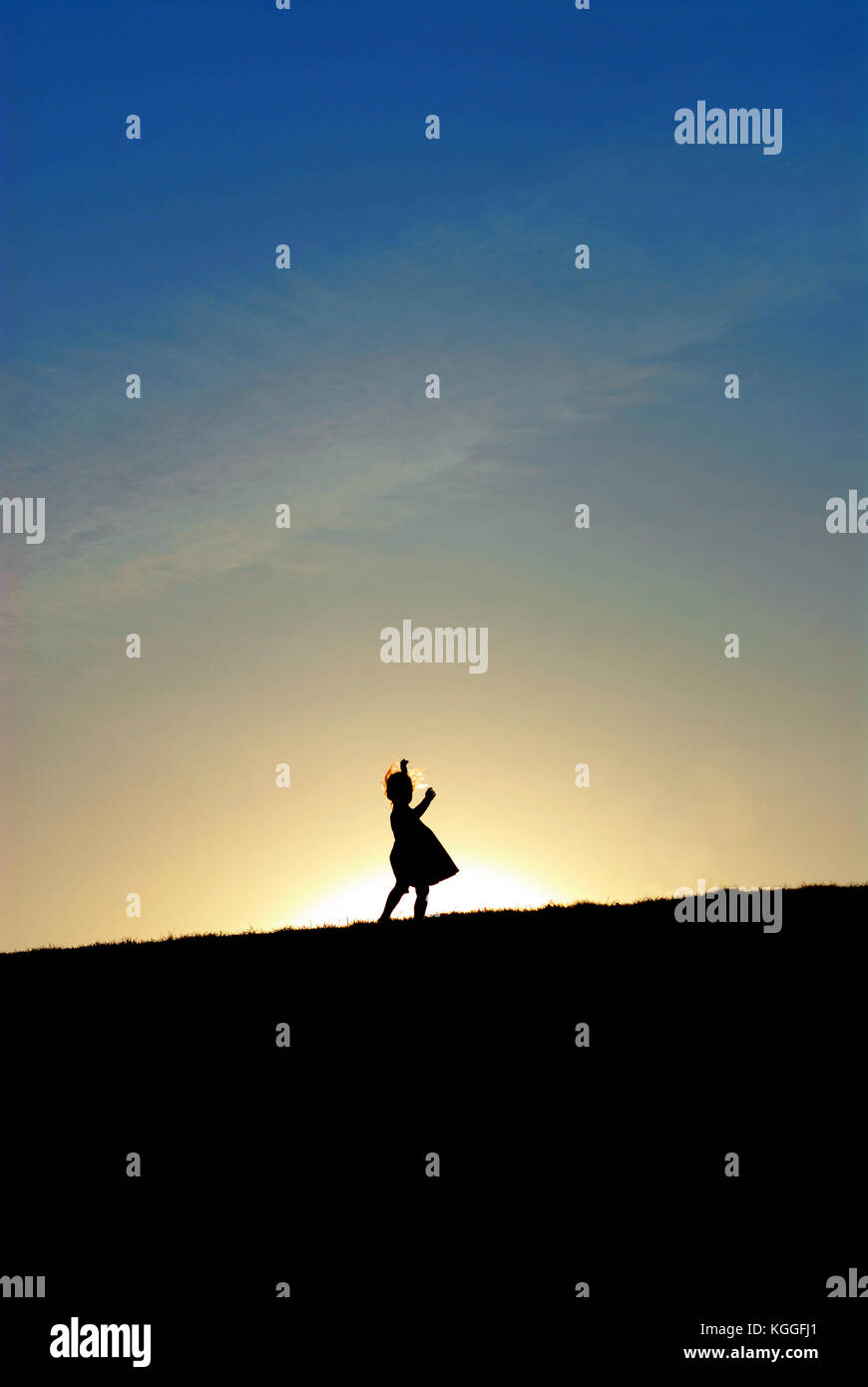 Silhouette of little girl dancing on the hill against the sun ...