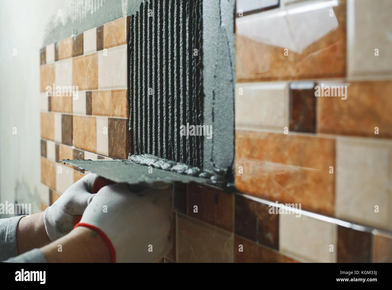 Laying ceramic tiles tiler deals tile adhesive on the wall stock laying ceramic tiles tiler deals tile adhesive on the wall dailygadgetfo Choice Image