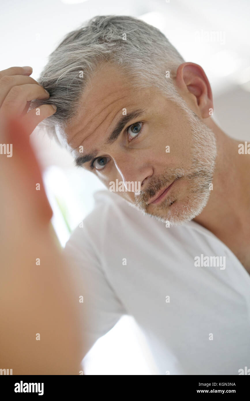 40 Year Old Man Checking Hair In Front Of Mirror Stock Photo
