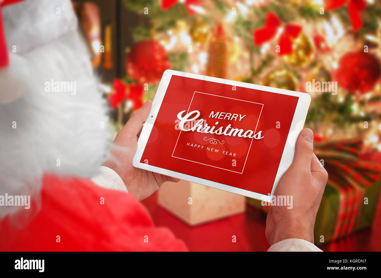 Santa Claus holding tablet with Merry Christmas greeting massage ...