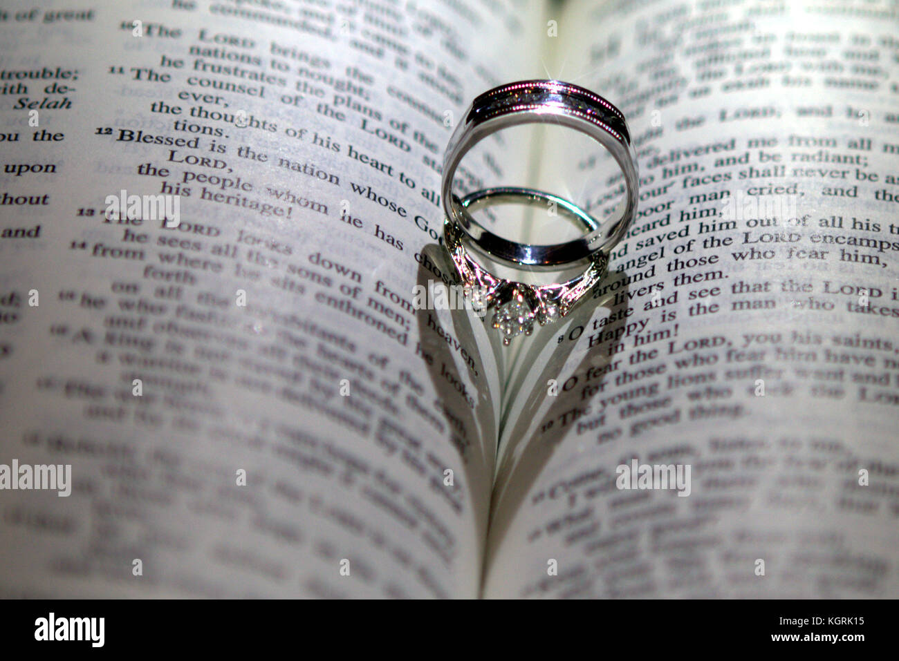 bible with wedding rings shaped as a heart stock photo 165247633