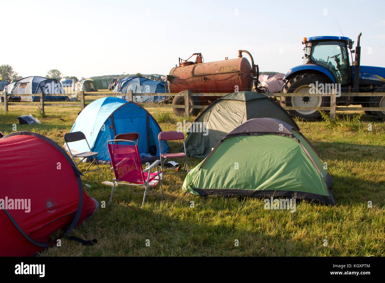 Tents at a music festival with a tractor and tanker in the background & Tents at a music festival with a tractor and tanker in the ...