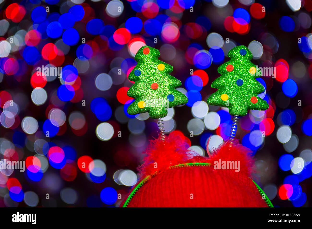 decorative springy christmas trees on novelty headwear standing against colorful bokeh light bubbles