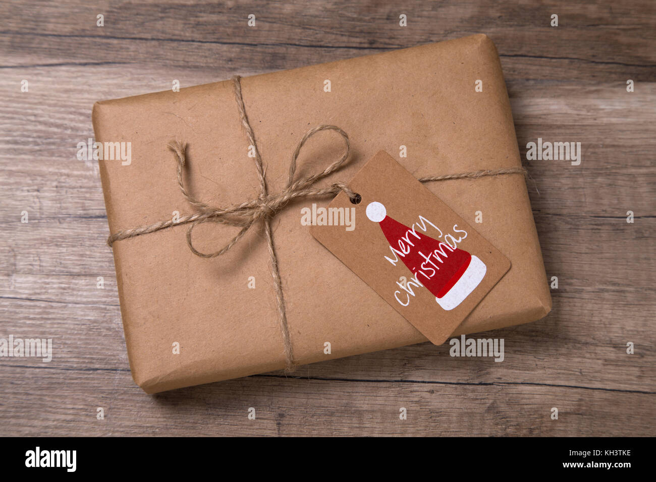 christmas or new year gift box wrapped in kraft paper with blank gift tag on old wooden background