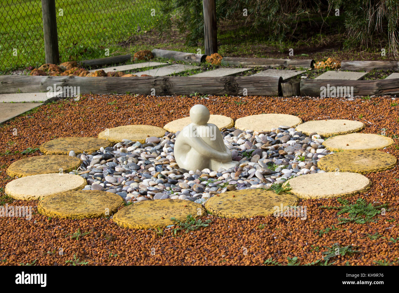 Ceramic Figure Sitting On Stones Encircled By Round Concrete Stepping  Blocks In A Garden Is Conducive