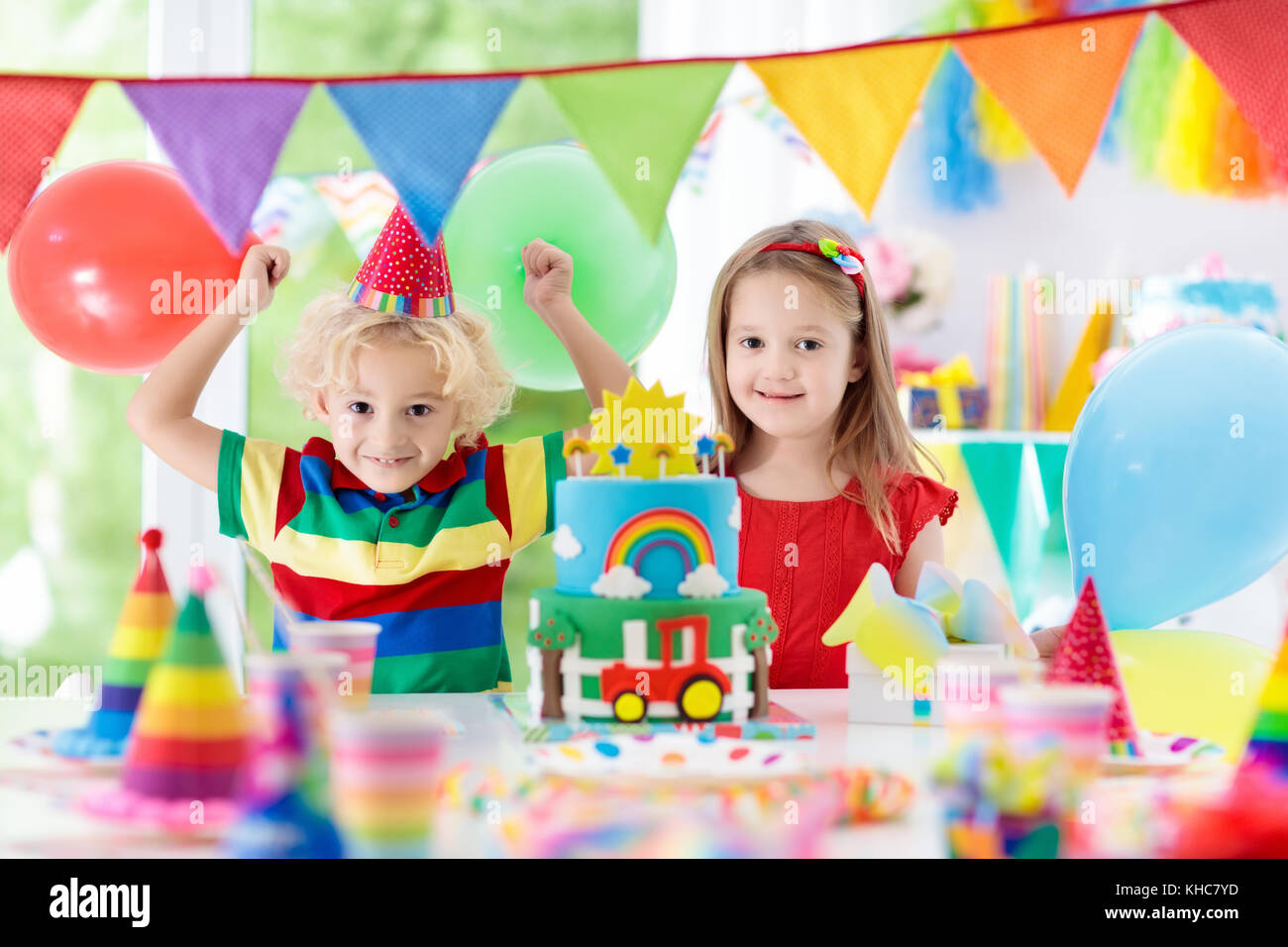 Kids Birthday Party Child Blowing Out Candles On Colorful Cake Decorated Home With Rainbow Flag Banners Balloons Confetti Farm And Transport Them