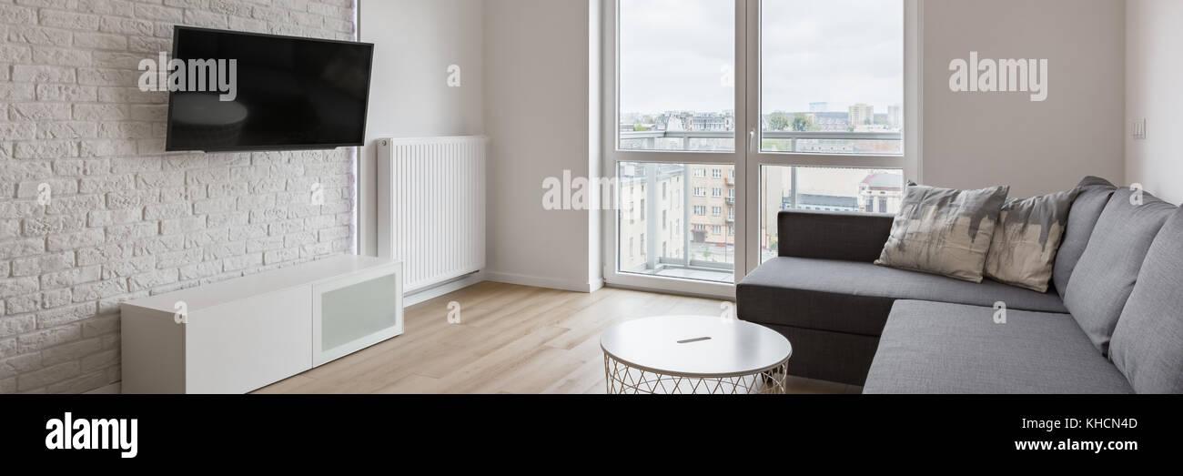 Living Room With Tv Sofa Balcony And White Brick Wall Panorama