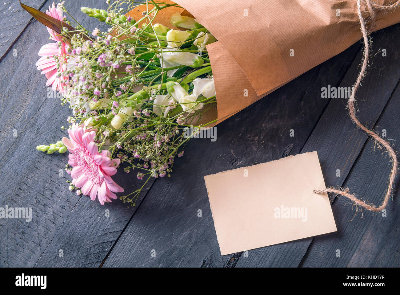 Greeting card idea with a cheerful bouquet of flowers wrapped in greeting card idea with a cheerful bouquet of flowers wrapped in vintage brown paper and an empty etiquette tied to it on a rustic wooden table mightylinksfo