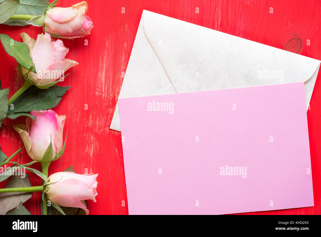 Greeting card idea with a pink paper on a closed envelope greeting card idea with a pink paper on a closed envelope surrounded by roses on a red wooden background a concept for mother day valentine day and m4hsunfo