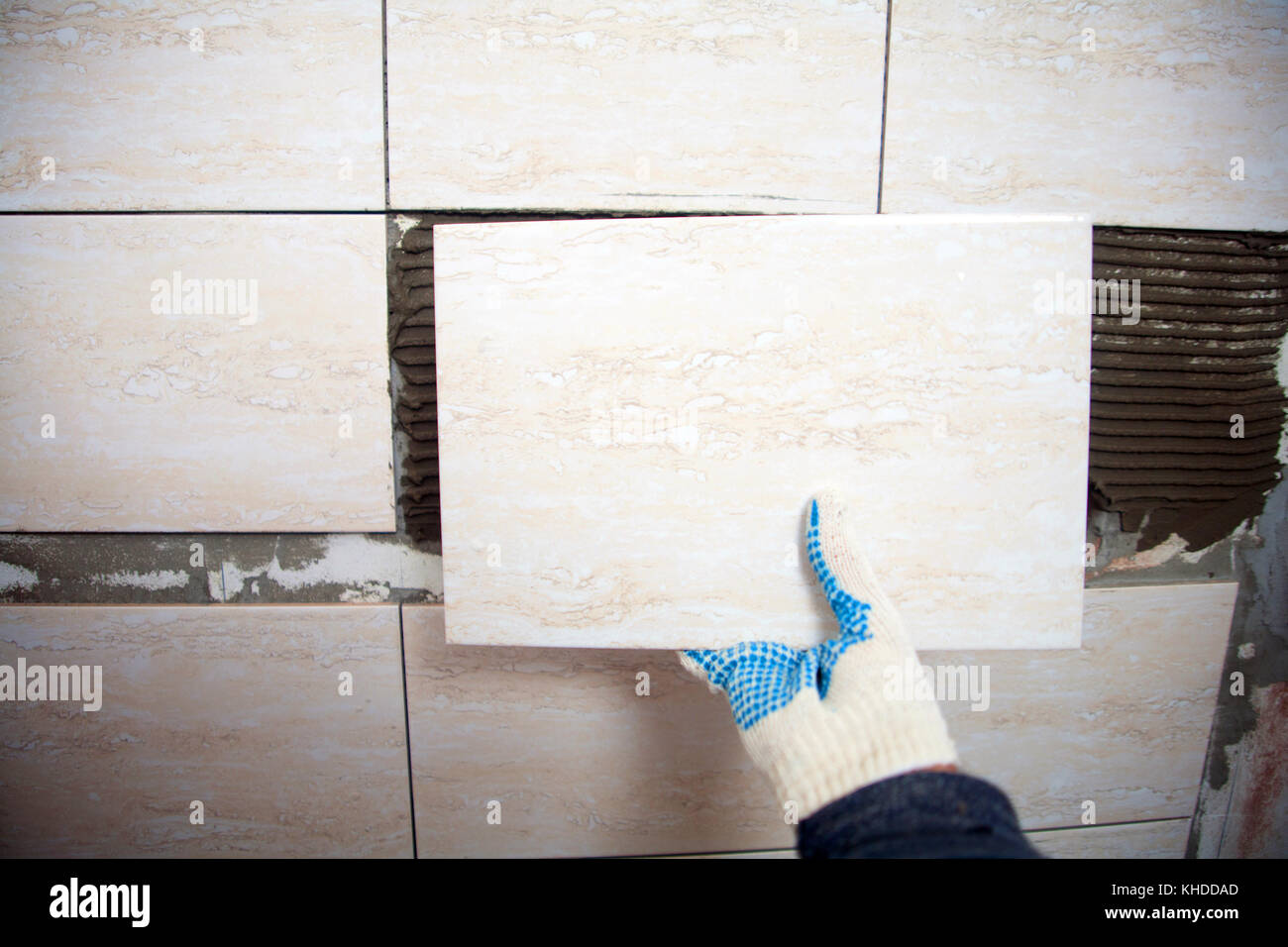 industrial construction worker installing small ceramic tiles on ...