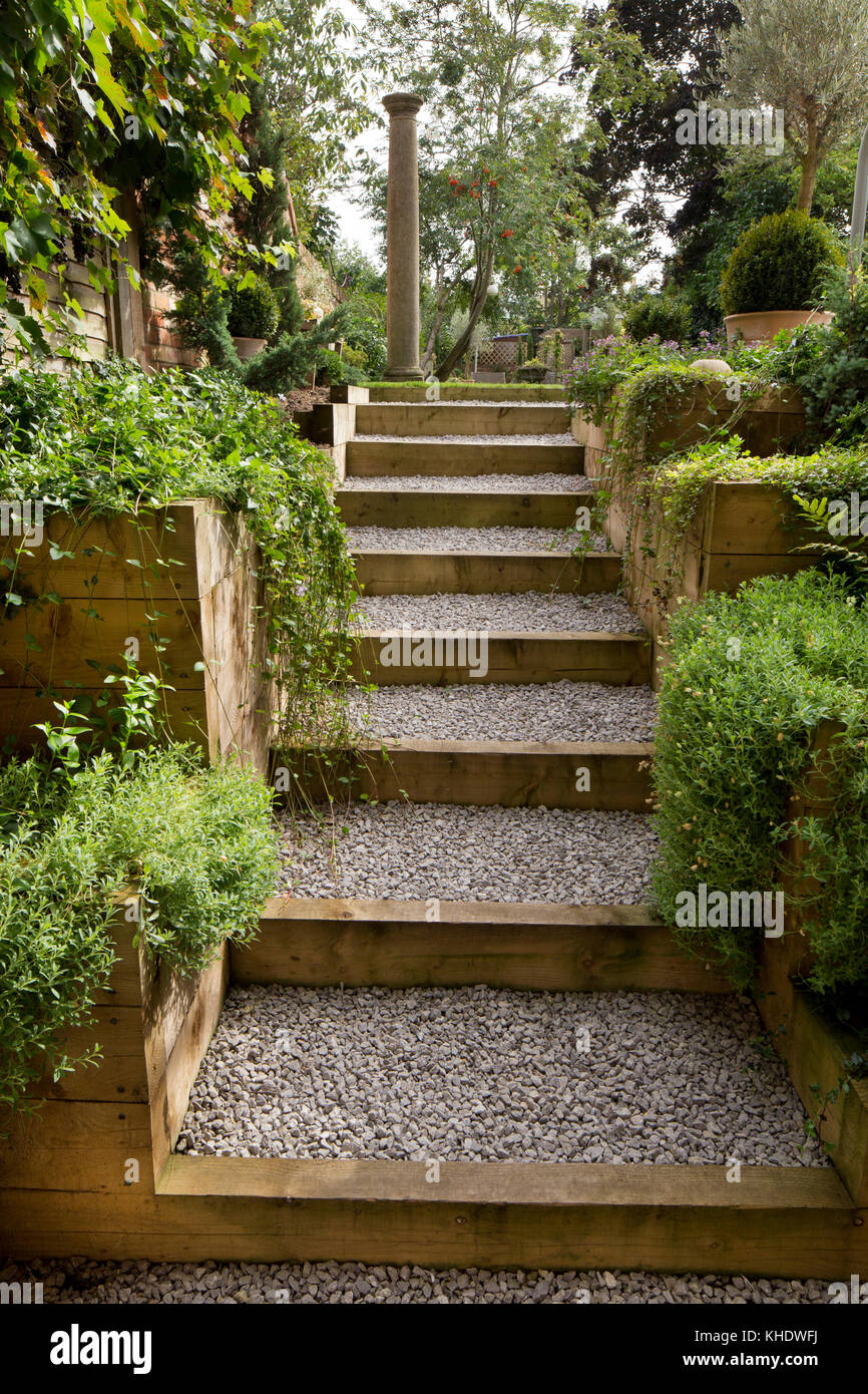 Gravel and wooden path leading up steps to garden on higher Stock ...