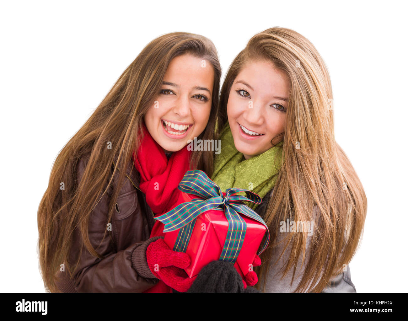 Mixed Race Young Adult Females Holding A Christmas Gift Isolated on ...