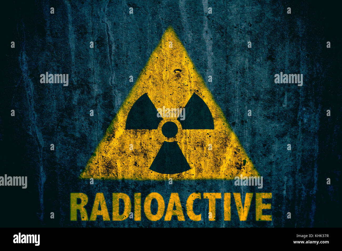 Triangular yellow and black radioactive ionizing radiation triangular yellow and black radioactive ionizing radiation danger symbol with word radioactive below painted on a massive concrete wall with dark ru buycottarizona Images