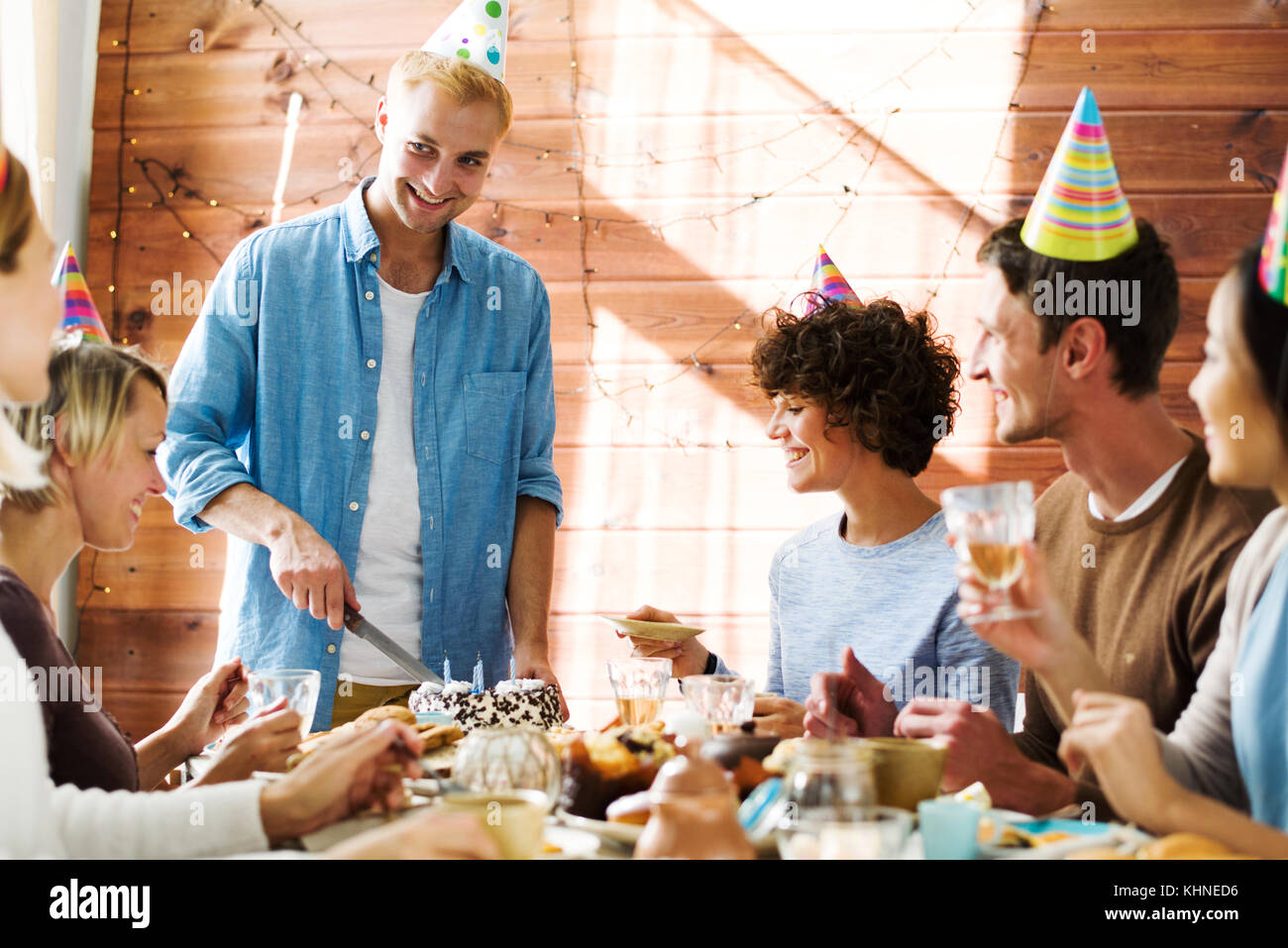 Young man cutting birthday cakes with candles among his friends by