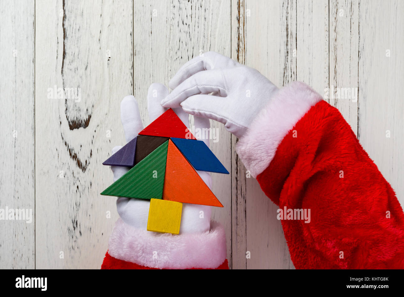 santa claus holding a christmas tree made by wooden tangram