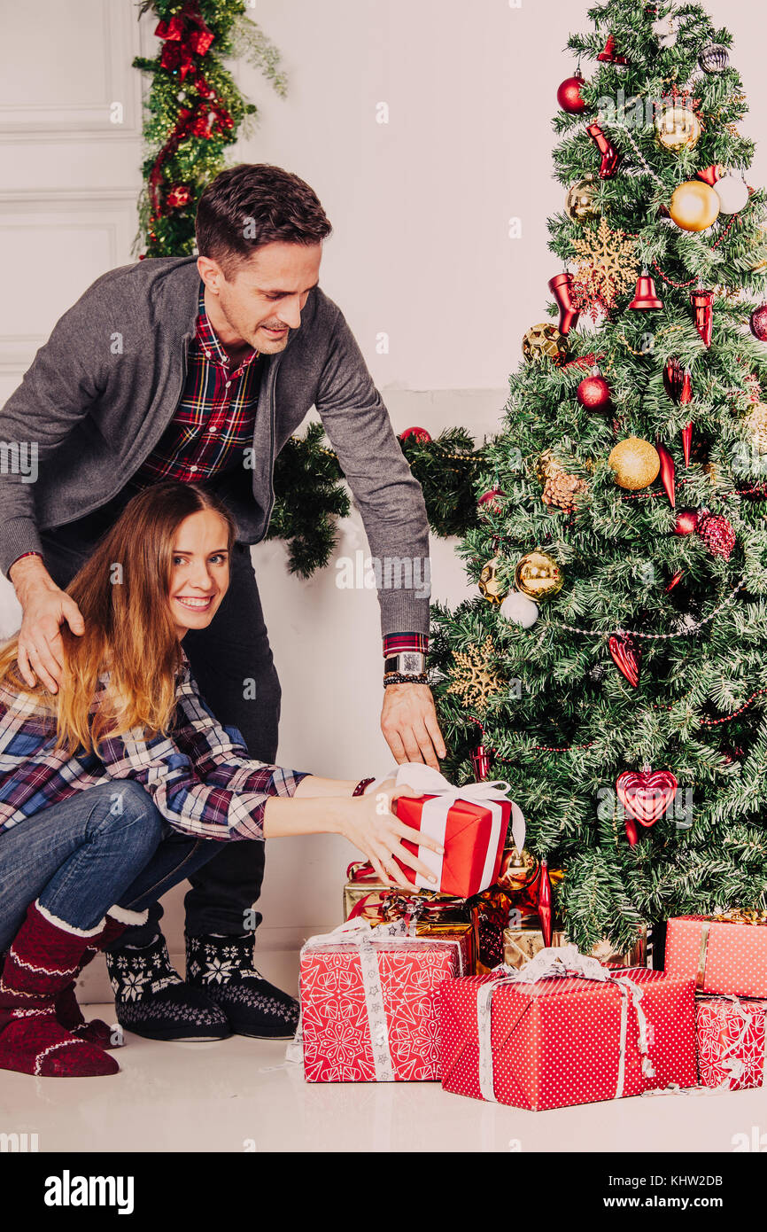 Happy parents put christmas gifts for children under decorated tree ...