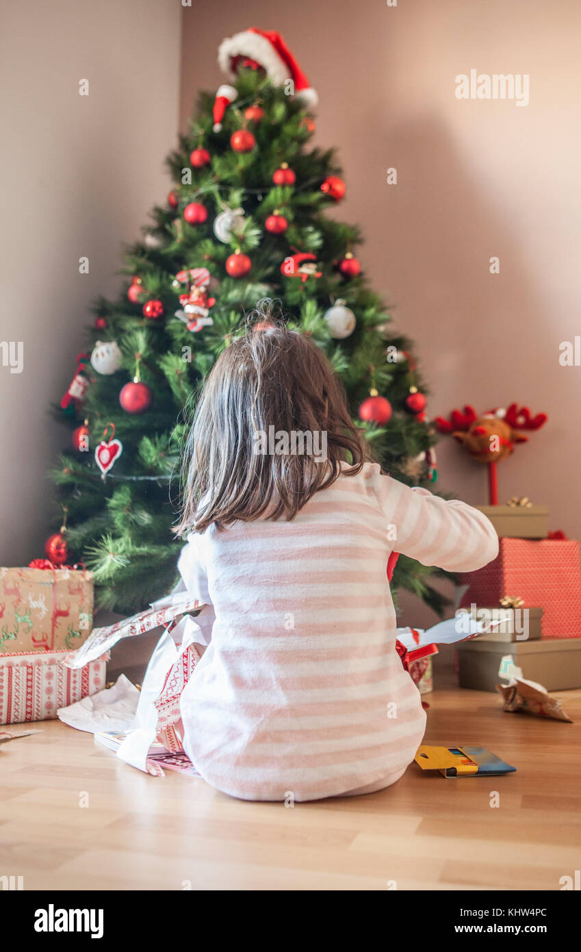 Little girl opening her gifts under Christmas tree early in the ...