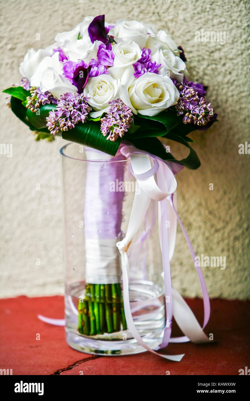 A Purple And White Bridal Flowers Bouquet In Clear Glass Vase