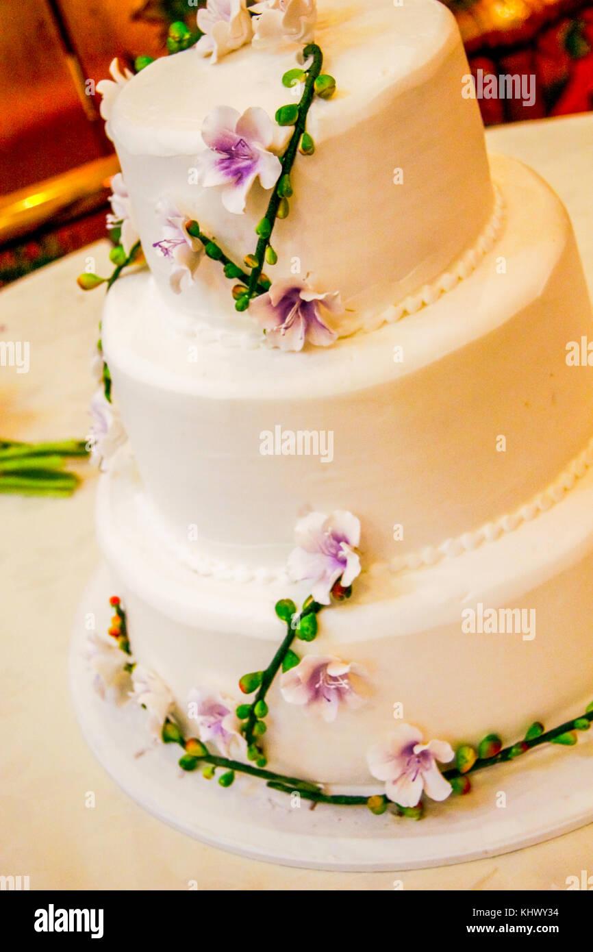 A Three Layered Wedding Cake With Fresh Flowers Wrapped Around It - Layered Wedding Cake