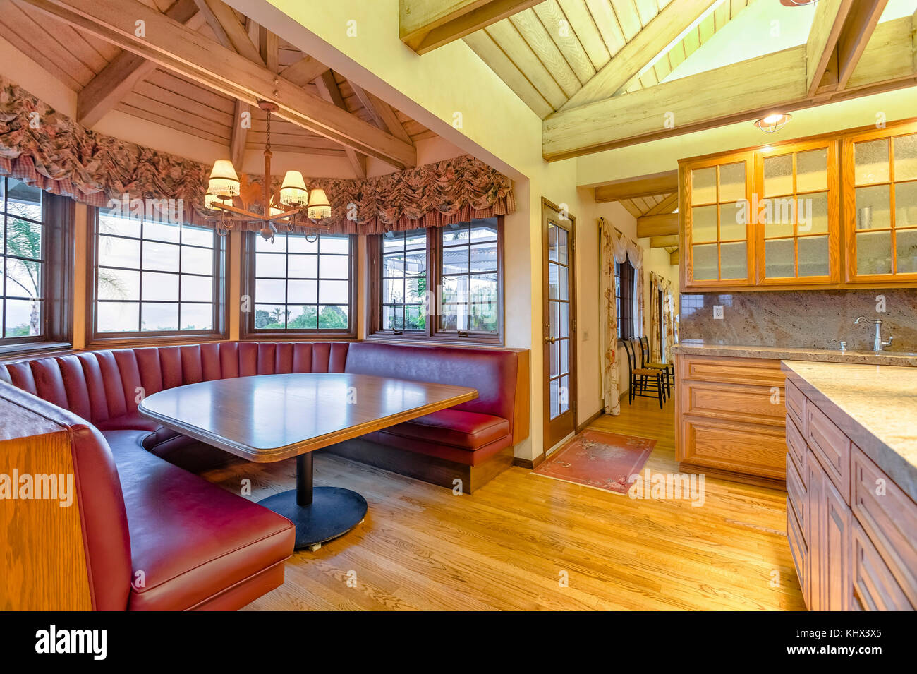 Bright Open And Warm Kitchen With Vaulted Ceilings And Booth Stock - Restaurant style kitchen table