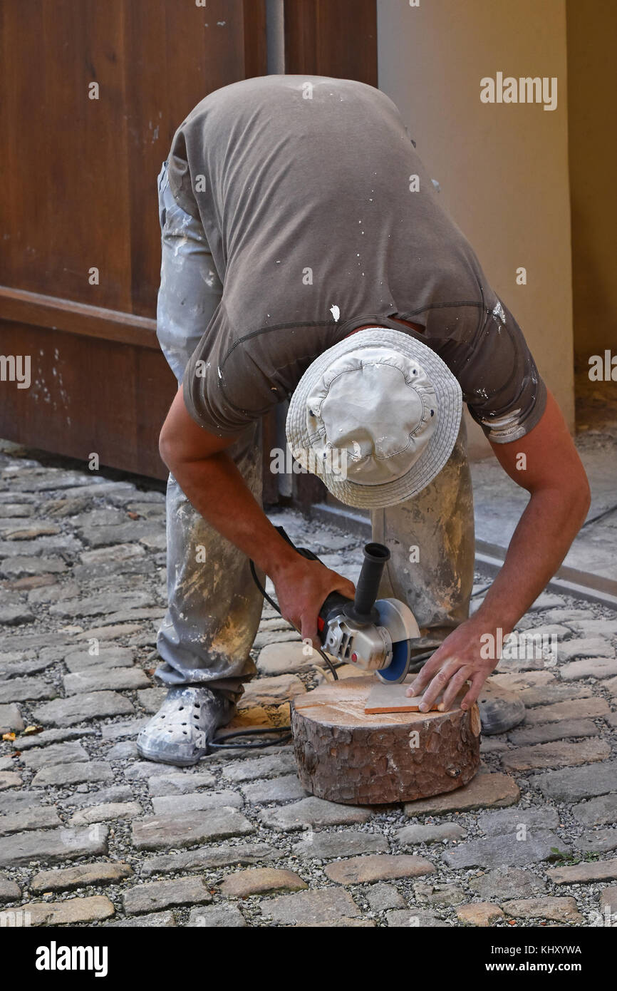 Close up of working man cutting and shaping ceramic tile with close up of working man cutting and shaping ceramic tile with angle grinder dailygadgetfo Image collections