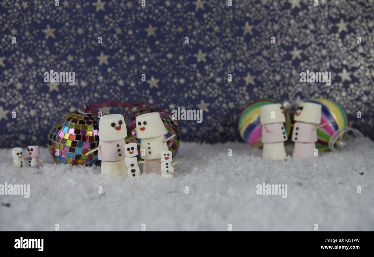 fun christmas food photography image using marshmallows shaped as happy snowman with iced on smile and standing in snow with color baubles and stars