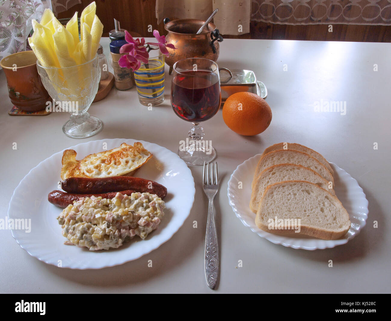 Table Served For Simple Breakfast With Bread Fried Eggs And Sausages On White Dishes