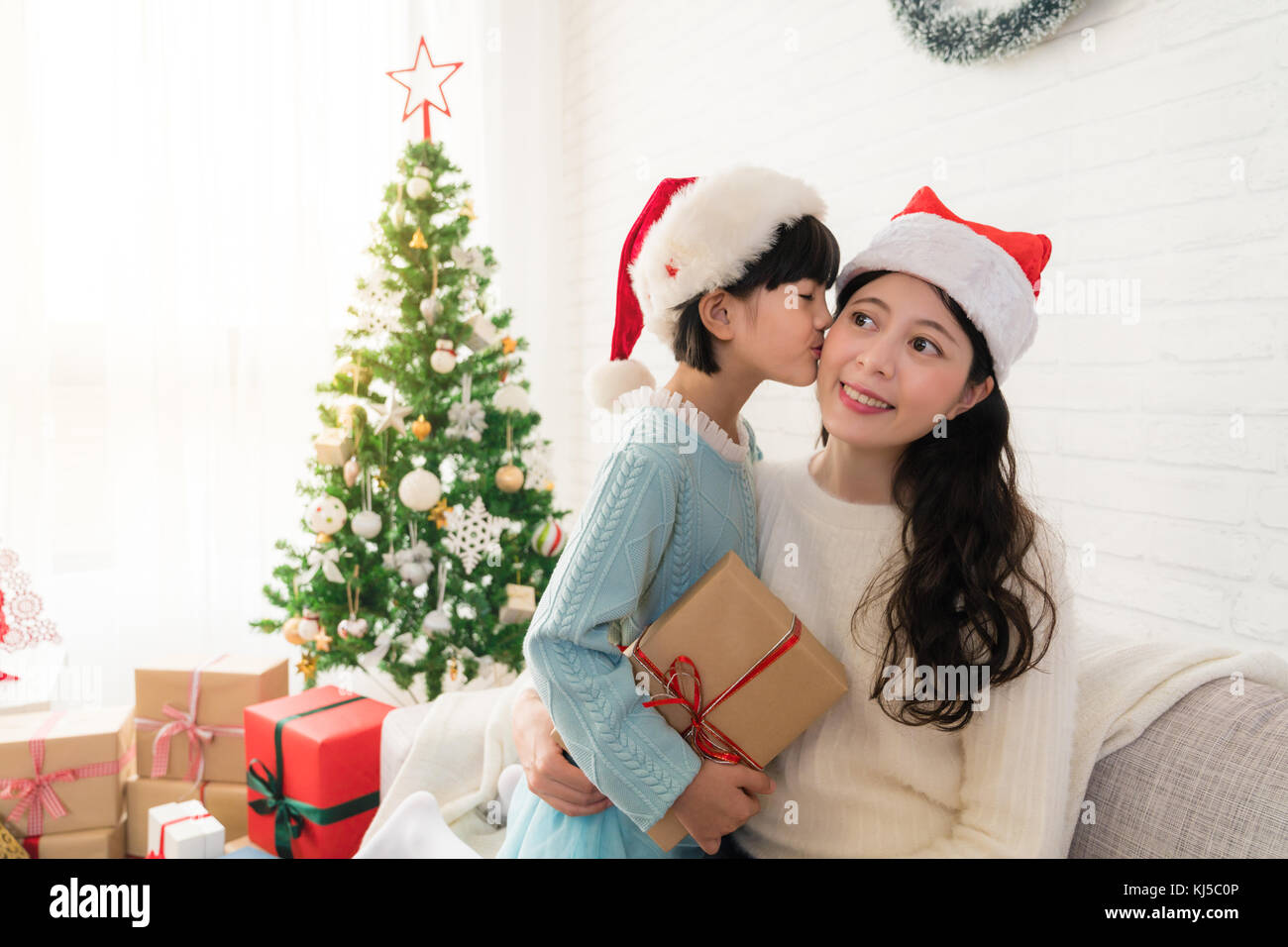 happy little Asian girl gives her mother a kiss thanks for the Stock ...